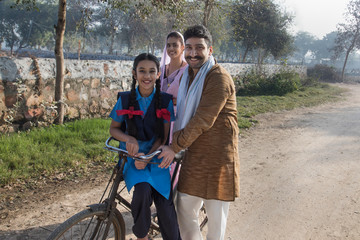 Happy rural family consisting of man, woman and a school going girl walking on street in a village.