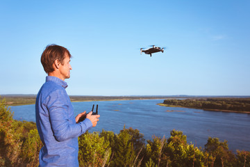 A man launches quadcopter. Flying drone over the river and forest on a sunny day