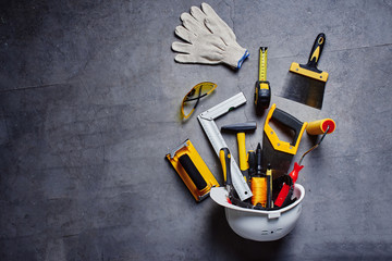 set of construction tools on a black wall background top view