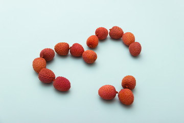 Red lychee heart shape on blue White Background.Valentines Day symbol Made of Red lychee