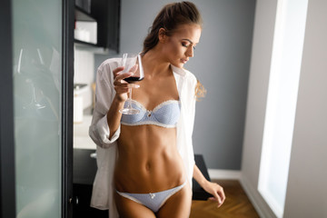 Sexy young woman in lingerie drinking wine at home