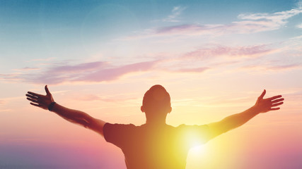 Young man standing outstretched at sunset. Victory Wall mural