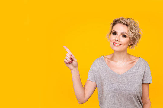 Model pointing upwards in studio and looking at camera. isolated orange background