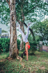 Sporty young woman doing handstand yoga exercise leaning on tree