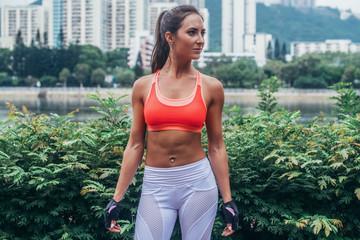 Full length portrait of tanned slim fitness brunette model wearing sports bra and leggings standing in the city park