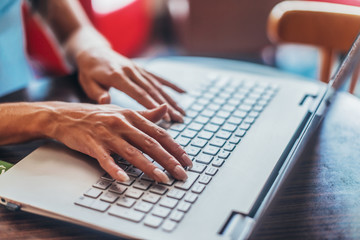 Close-up shot of female hands typing on laptop keyboard