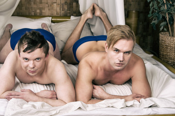 Two adult guys relaxing in bed. Couple. Love and relationship.