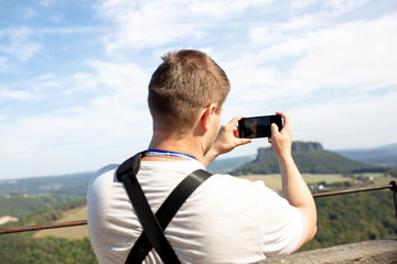 Man uses his mobilephone outdoor,taking a photo in the landscape park
