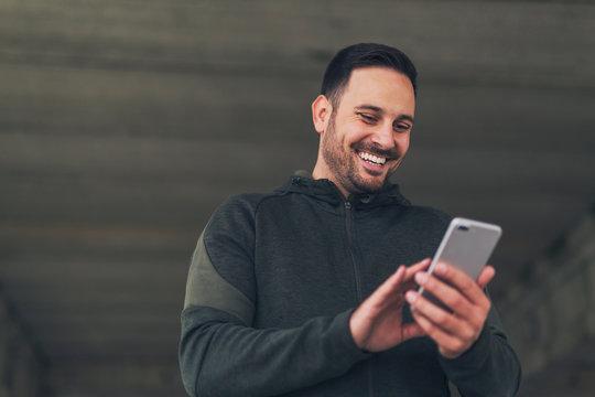 Man in sportswear using phone.