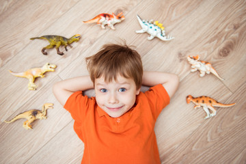 Little boy lying on the floor with a collection of dinosaurs