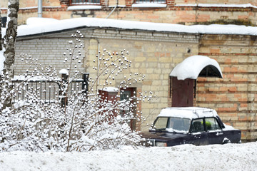 The car is parked in front of an old building in the winter city.