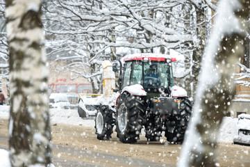 Snowplow cleans the road in the city from snow in winter
