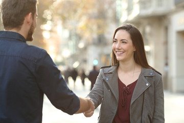 Happy man and woman handshaking in a city street