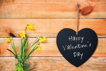 Poster Vintage Poster Happy valentine's day written on a chalkboard in the shape of a heart, daffodils and wooden planks background