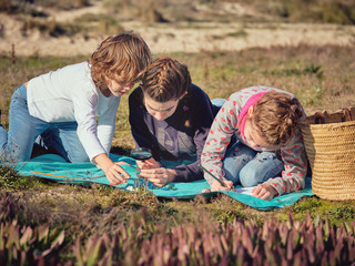 Woman taking notes and children gauging little things on coverlet