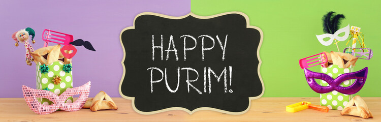 Purim celebration concept (jewish carnival holiday) over wooden table and purple green background.
