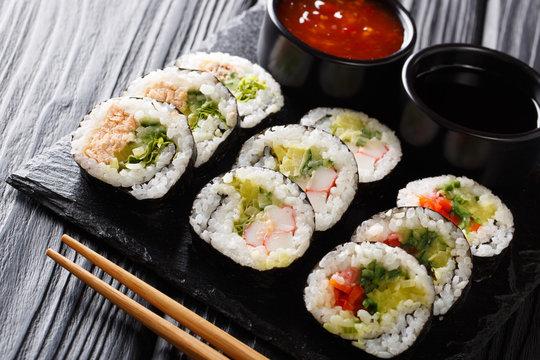 Japanese rolls set close-up served on a slate board. horizontal