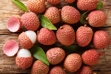 Fresh lychee and peeled showing the red skin and white flesh with green leaf. Horizontal top view