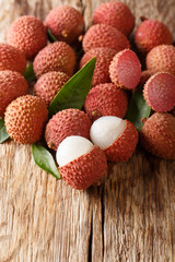 Lychee fruits with green leaves close-up on a wooden table. vertical