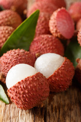 Ripe lychee fruits with green leaves close-up on wooden. vertical
