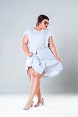 Plus size fashion model in striped dress, fat woman on gray background