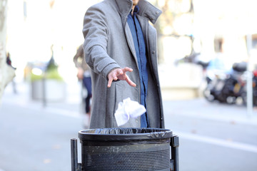 Man hand throwing paper into trash bin