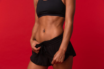 Cropped photo of african american woman in black sportswear standing, isolated over red background