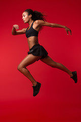 Portrait of energetic african american woman in black sportswear running, isolated over red background