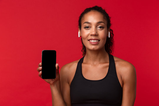 Portrait of feminine african american woman in black sportswear using smartphone and wireless earphones, isolated over red background
