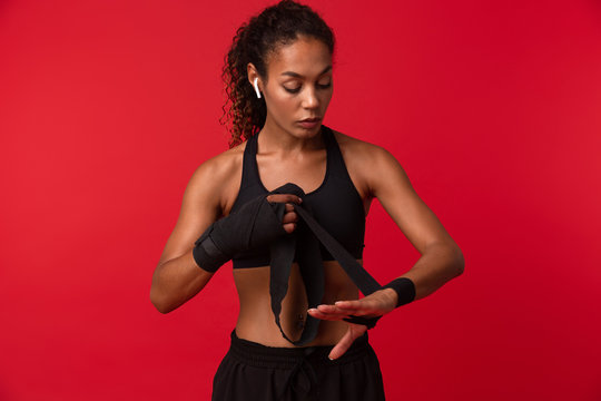 Image of fitness african american woman in black sportswear wearing sports bandages on her hands, isolated over red background