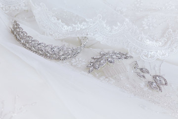 Crystal jewellery: earrings, hairpin, diadem on a white wedding background. Wedding jewelry. Tiara. Selective focus. Collection