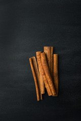 Spoed Foto op Canvas Kruiderij Bunch of cinnamon sticks on blackboard background with chalk smudges texture. Vintage rustic style. Holiday baking beverages ingredient. Healthy spices concept. Copy space