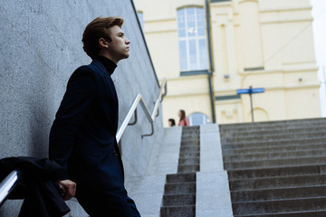 a man stands leaning on a gray wall about a railing, in a dark blue suit, next to it, on a railing, a coat is hanging, on the street. Stairs up. Stage in life.