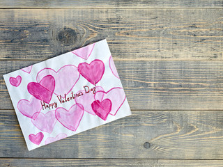 Children's drawing with hearts and an inscription for Valentine's day, lying on wooden textured boards of light gray color