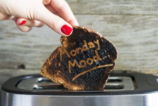 Monday mood concept with slice of burned toast bread in woman hand