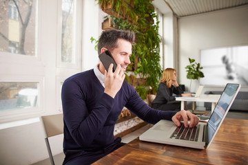 Businessman with making a call and working on laptop while sitting in the office