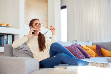 Lovely young woman talking with somebody on her mobile phone while sitting on sofa at home