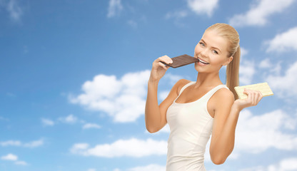 slimming and diet concept - happy woman eating dark chocolate instead of white over blue sky and clouds background