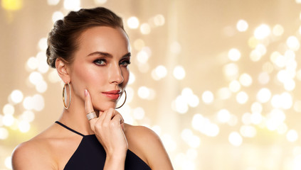 luxury, jewelry and people concept - beautiful woman in black wearing diamond earring and ring over beige background and festive lights