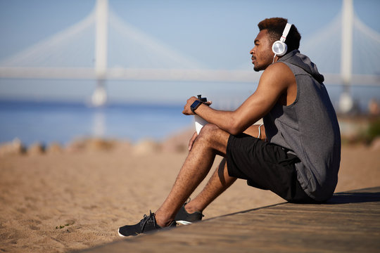Serious thoughtful young black man in gray sleeveless hoodie sitting on ground and listening to music via wired headphones while resting after training on beach