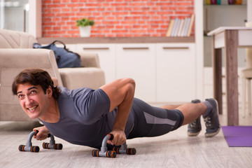 Young handsome man doing sport exercises at home