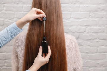 Close-up drop oil restore and recovery hair is applied to head bulbs. Concept hairdresser spa salon