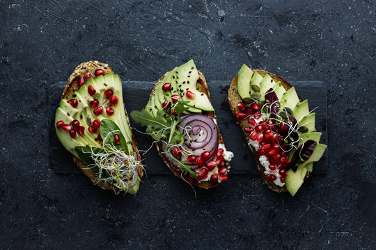 Healthy avocado toasts with avocado slices, pomegranate seeds and sprouts on dark background.