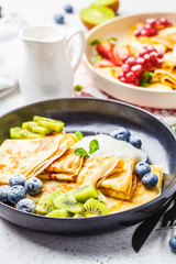 Homemade thin crepes served with curd cream, fruits and berries in black and white plates.