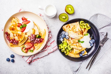 Homemade thin crepes served with curd cream, fruits and berries in black and white plates, top view.