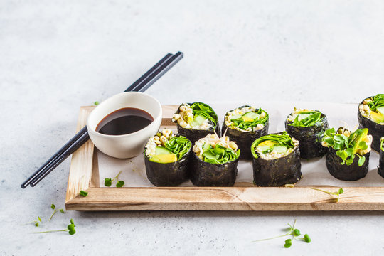 Green vegan sushi rolls on wooden board.