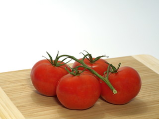 0637 tomatoes, shrub tomatoes with stems, large, on a wooden board against a white background