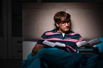 Young student preparing for exams at night at home