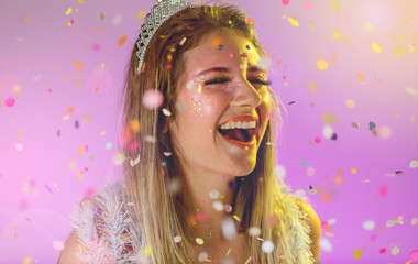 Carnaval Brazil. Throwing confetti. Face of young woman with colorful makeup, dressed up for fun. Bright background. Party concept, celebration and festival.