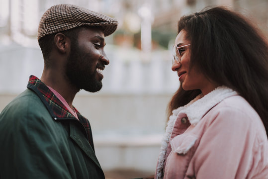 Young smiling beloved couple look to each other
